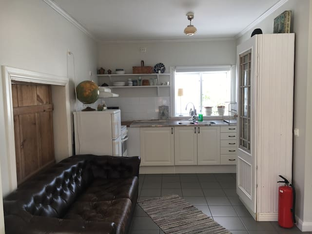 Kitchen with fridge/freezer, coffee maker and stove. Crockery, cutlery, pots and pans.