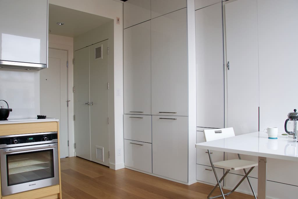 """Kitchen/dining area *fridge and freezer located in small drawers **wall-bed is in the """"up"""" position"""