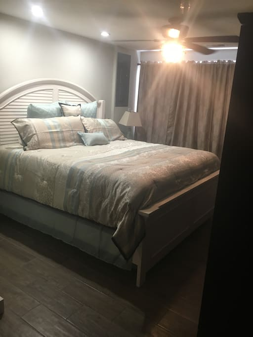Master bedroom with large wardrobe cabinets and smart television.