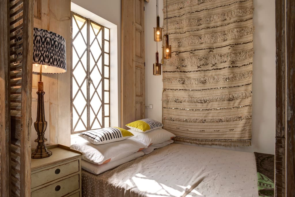 Comfy double bed with Moroccan wedding blanket hanging behind & church window for an intimate and elegant night's sleep!