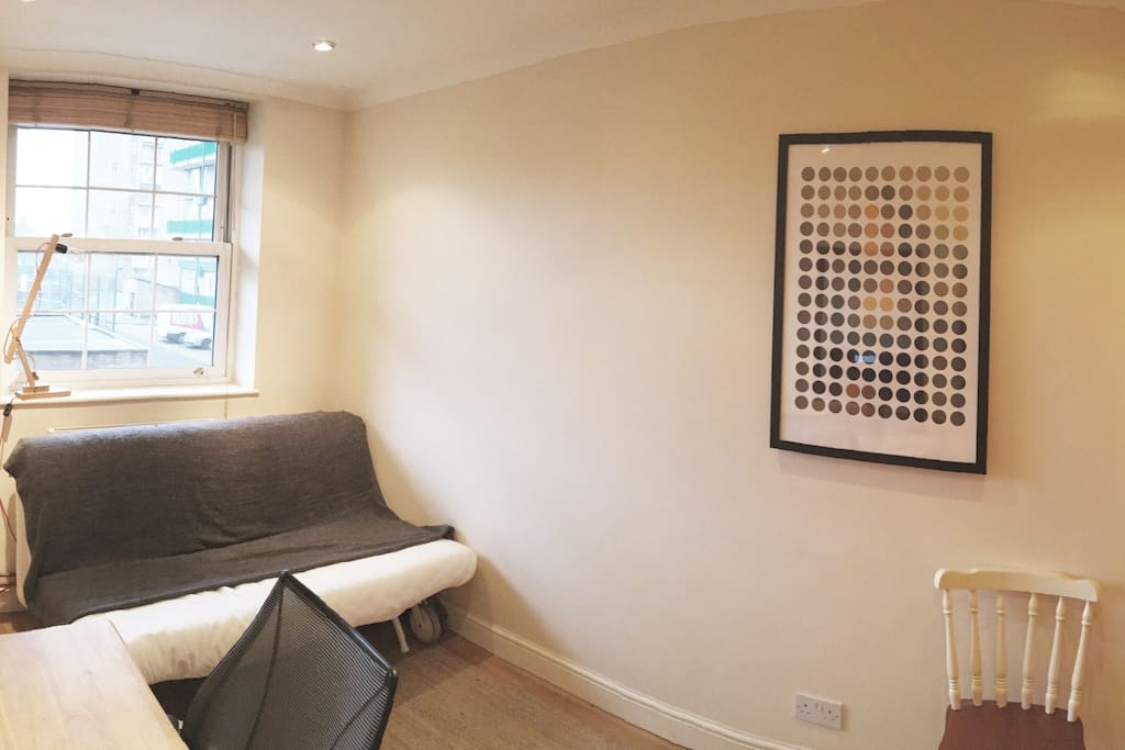 Second bedroom has a quick-fold sofa bed, a baby cot and a work desk
