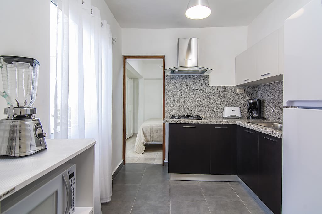 Kitchen with stove, refrigerator, microwave, blender, coffee machine, toaster etc.