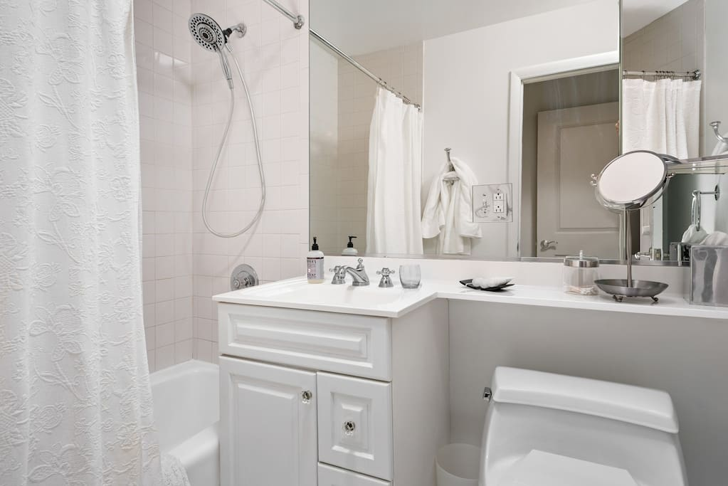 All white bathroom with tub and shower.