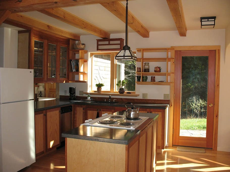 Kitchen with electric range and concrete countertops.