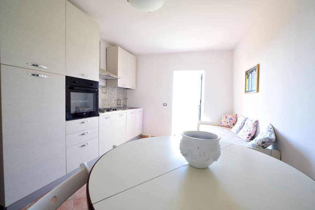 Ingresso con cucina e angolo relax. Accesso al giardino.  Entrance with kitchen and relax corner. Access to the garden.
