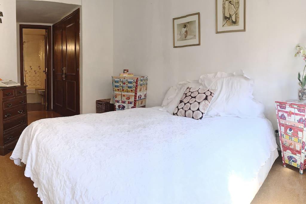 Habitación muy luminosa con cama matrimonial grande y baño en la habitación