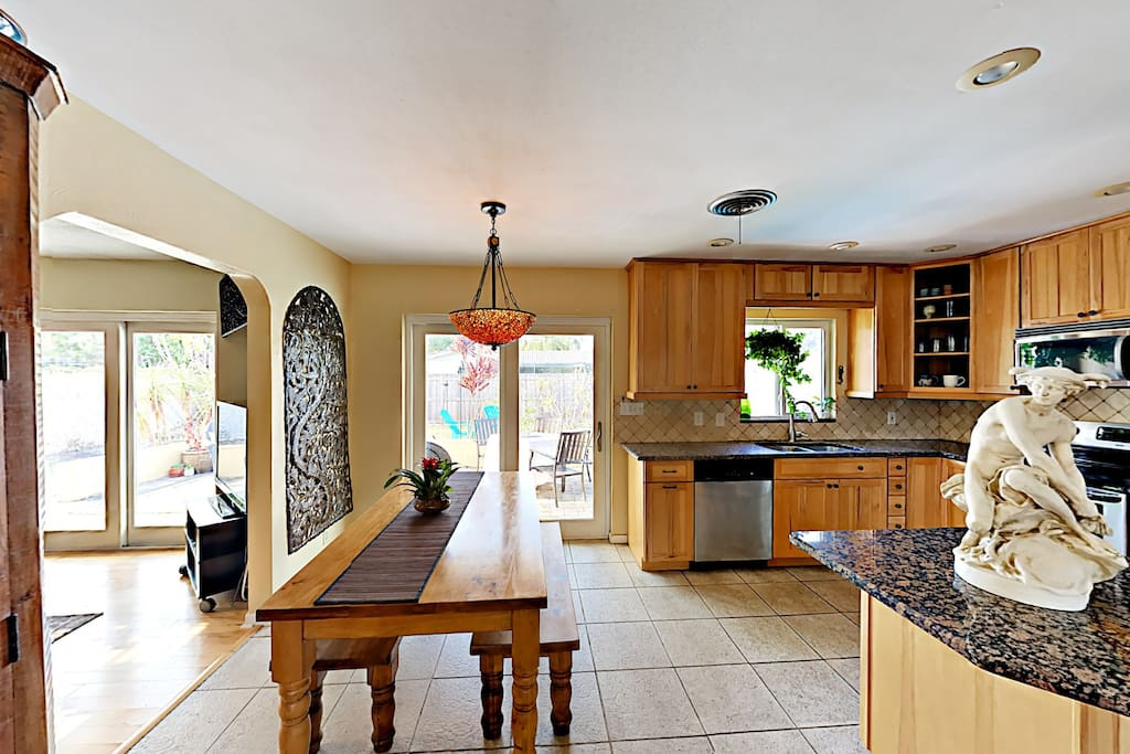 The open kitchen is outfitted with granite counters and a large island