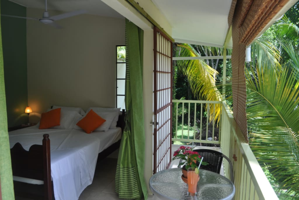 The Rainforest bedroom, giving on to a private balcony which overlooks and orchard of coconut palms and mango tree, beyond which is rainforest