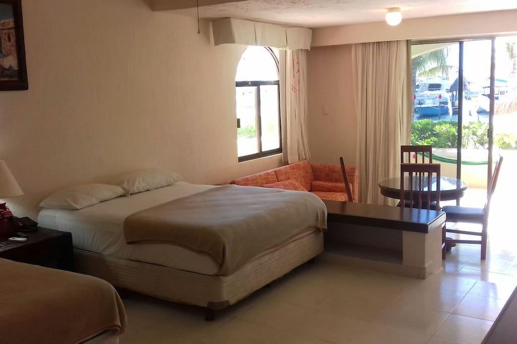 Cuenta con dos   camas matrimoniales  un sofa  cama  una mesa  con cuatro   sillas  y una pequeña  cosina y desde  ahí puedes apreciar  la playa