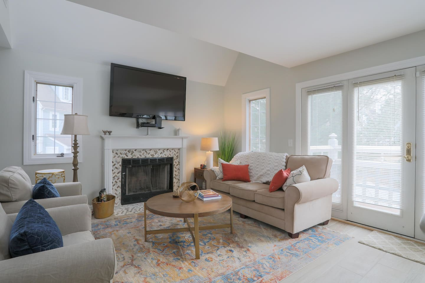 Living room area with working fireplace and large screen TV. Doors to balcony.