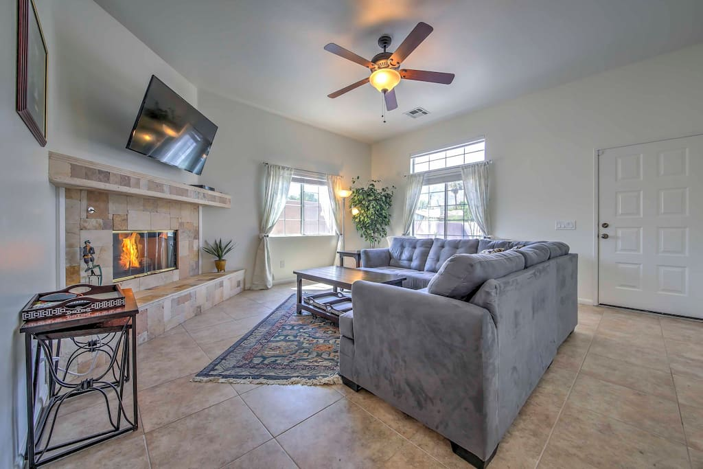 Lounge around the living room which features a large sectional couch, a gas-burning fireplace, and a flat-screen cable TV.