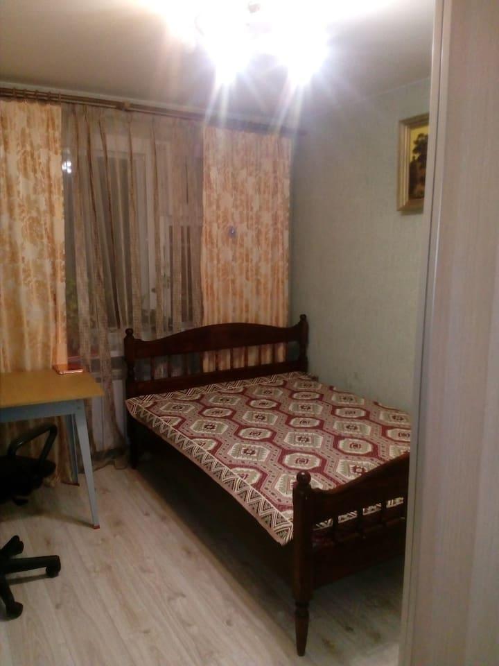 С двуспальной кроватью, платяным шкафом и столом.