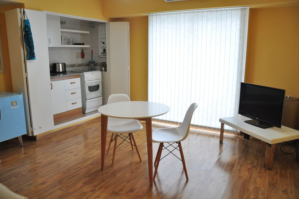Vista Interior: Mesa y sillas +  Cocina + Mesa de Arrime + TV.