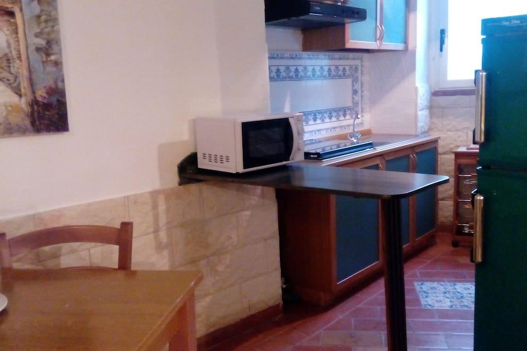 cucina con accessori  frigo microonde posate  piatti pentolame vario tavolo