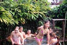 Familia disfrutando de las aguas calientes en tina de madera.