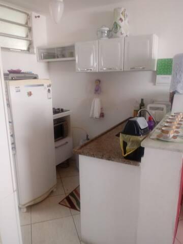 Cozinha equipada com geladeira, cooktop, microondas, liquidificador e espremedor de frutas.