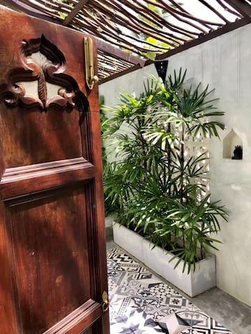 Antique doors welcome you to your private indoor/outdoor master-bedroom bathroom. Enjoy exhilarating rain-shower under the sun or stars surrounded by lush tropical vegetation.  The toilet area is covered.