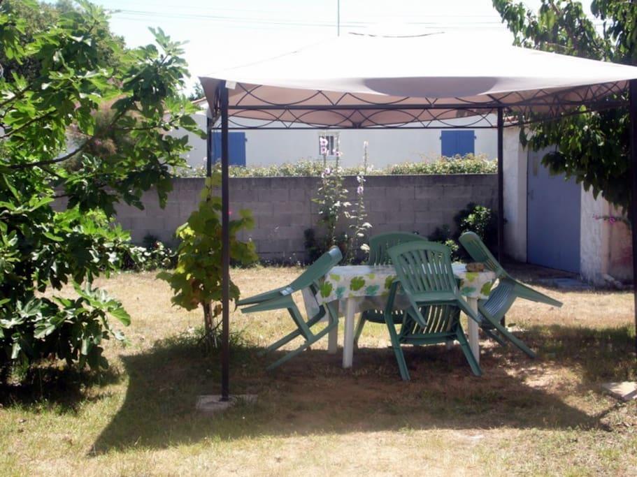 Coin arboré  avec salon de jardin pour des déjeuners à l'extérieur
