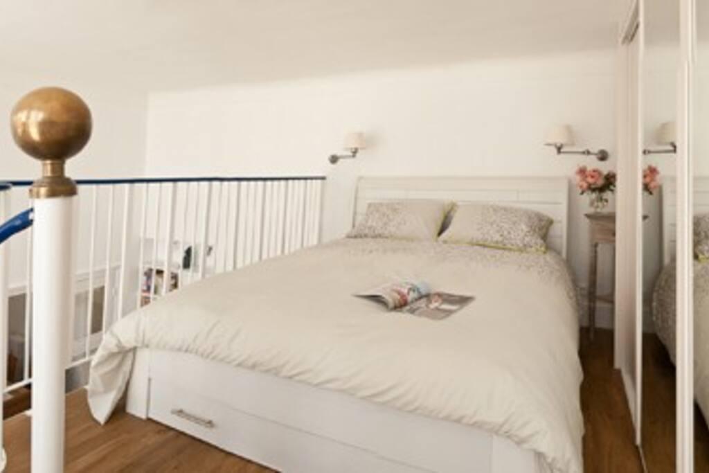La chambre avec sa vue sur les toits de Paris et la Tour Montparnasse.