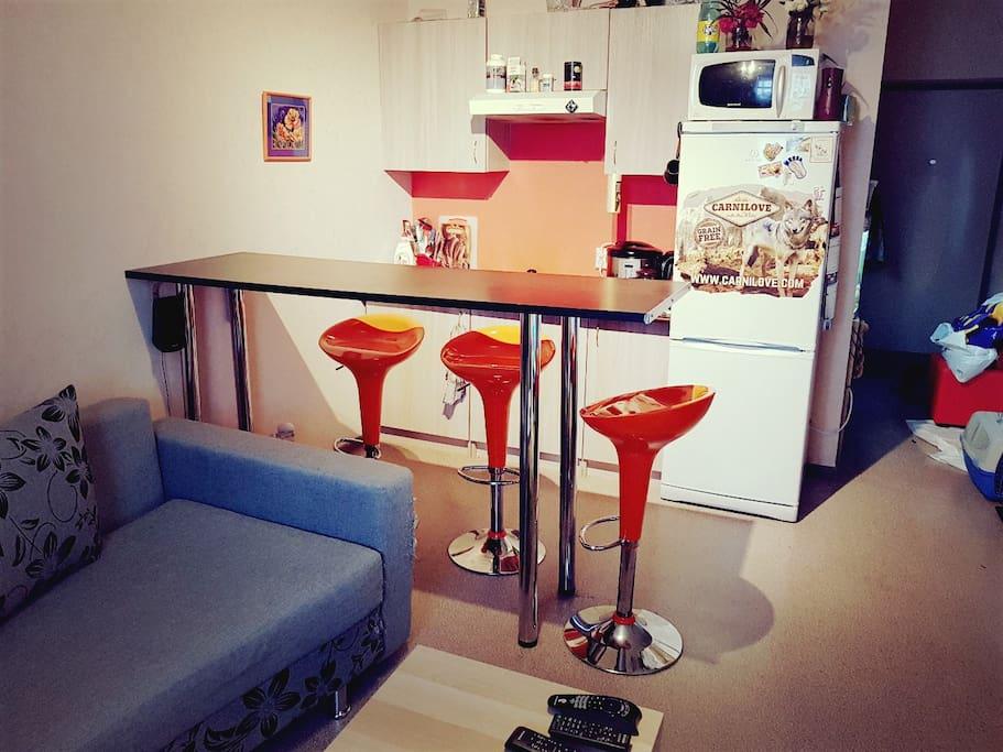 В квартире полноценная оборудованная кухня и барная стойка с темя стульями