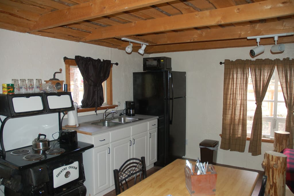 Tranquility Cabin Kitchenette with stove top, microwave, refrigerator and table for two