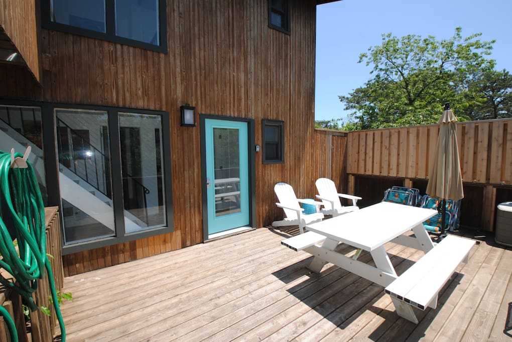 This is the first floor entry deck featuring a picnic table with seating for 6 and 2 Adirondack chairs