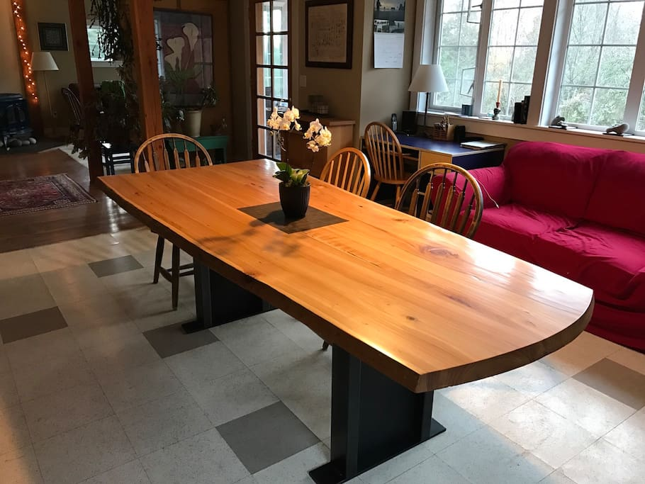 Live-edge cedar dining table in a light-filled common  room