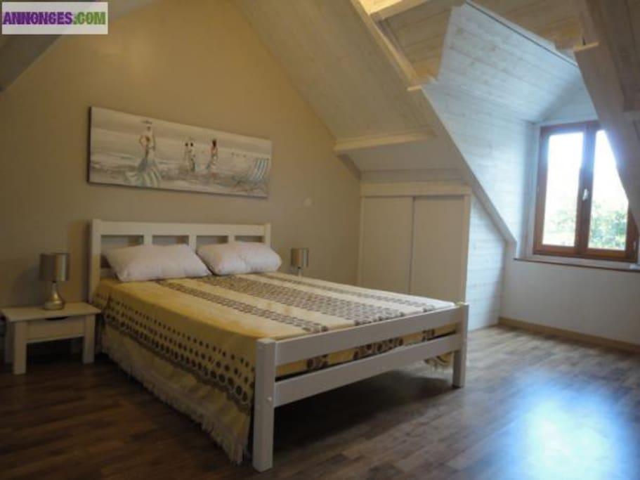 Chambre avec grand lit, lit bébé et table à langer