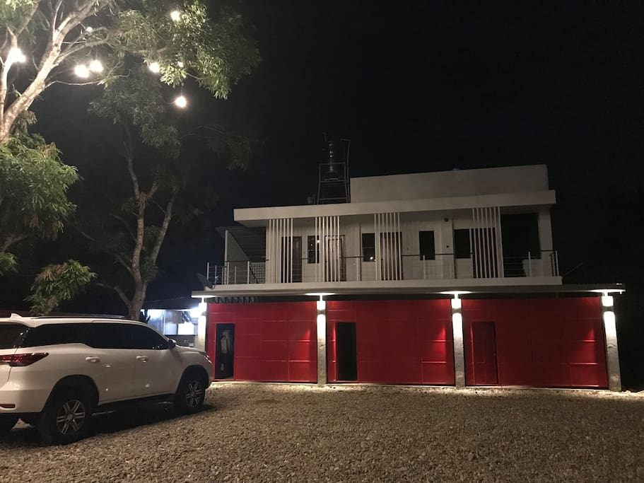 This is the building. It has own garage for your car or just use it extra private space. Small lights are attached to mango tree to lighten up place.