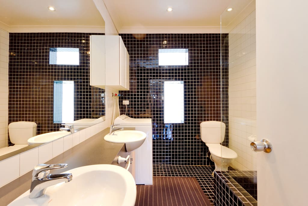 Sparkling central bathroom with 2 vanity basins, washing machine, shower and bath.