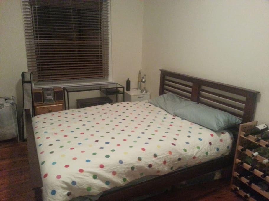 Queen bed and desk in the bedroom.