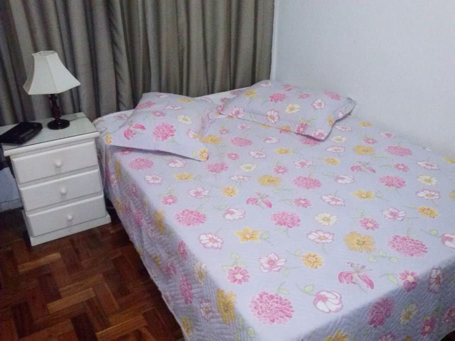 Quarto com cama de casal e mesinha lateral