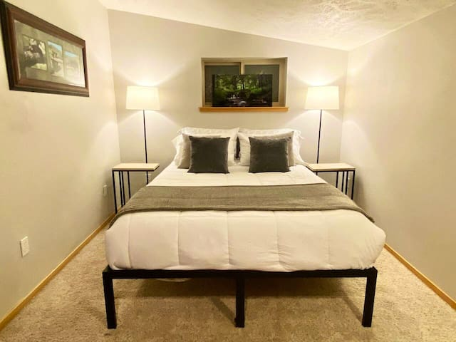 Upstairs bedroom with queen bed and closet plus extra shelving.