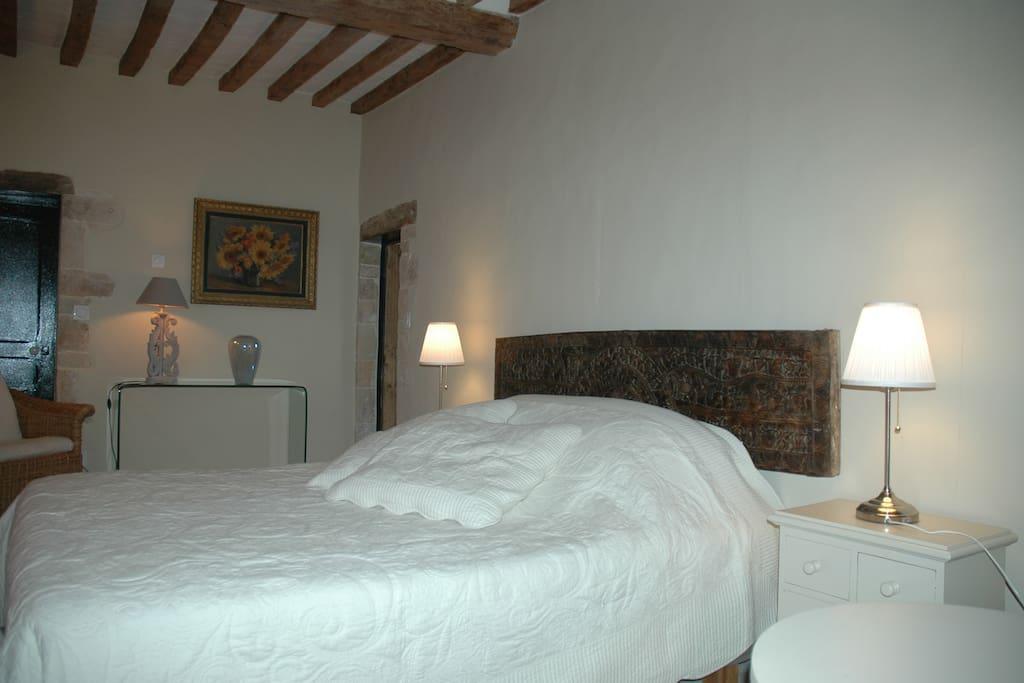 Un grand lit confortable avec douche et toilettes attenantes
