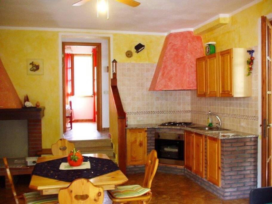 soggiorno con angolo-cottura, caminetto e vista di 1 camera letto