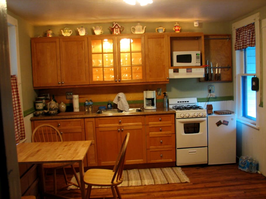 Remodeled kitchen. The wainscoating, chair rail, and old maple floor preserved with upgrade on cabinets and appliances.