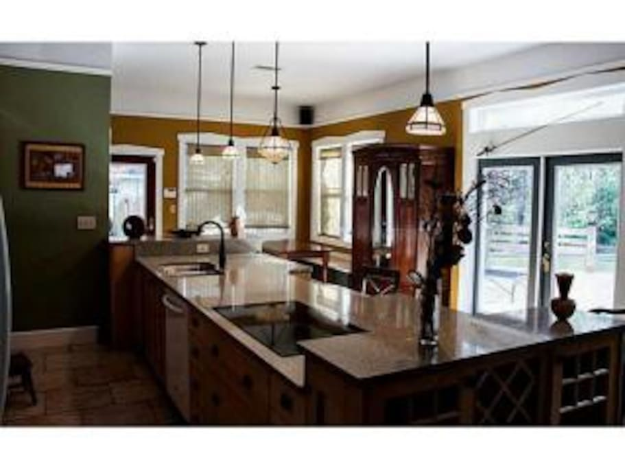 Fully stocked kitchen looks out onto deck and woods. Cook your heart out with an amazing view!