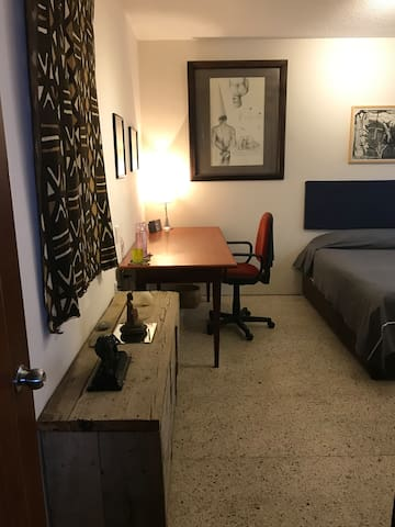Es una habitación amplia, con su escritorio de caoba, cama queen size con memory foam, TV, cajones disponibles, baño con acabados de lujo y mucho arte en las paredes.