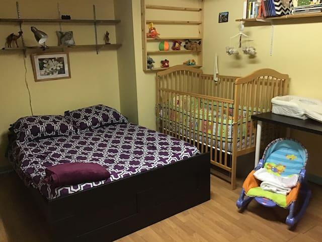 Chambre familiale avec lit de bébé et lit simple