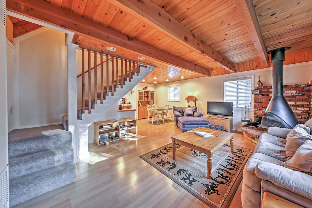The spacious living area offers comfortable seating and a wood-burning fireplace to stay warm on chilly nights.