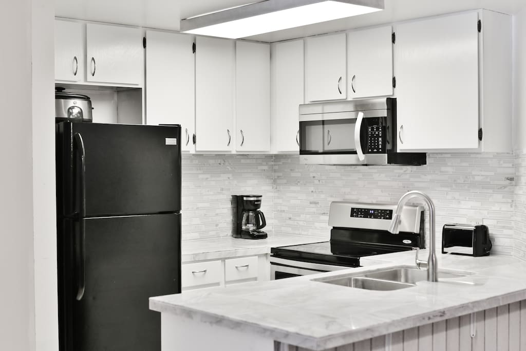 Remodeled kitchen with marble countertops, new sink, faucet and appliances