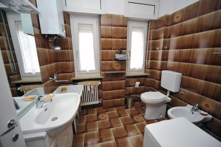 Bathroom with vintage tiling complete with sink, wash basin, toilet and bidet.