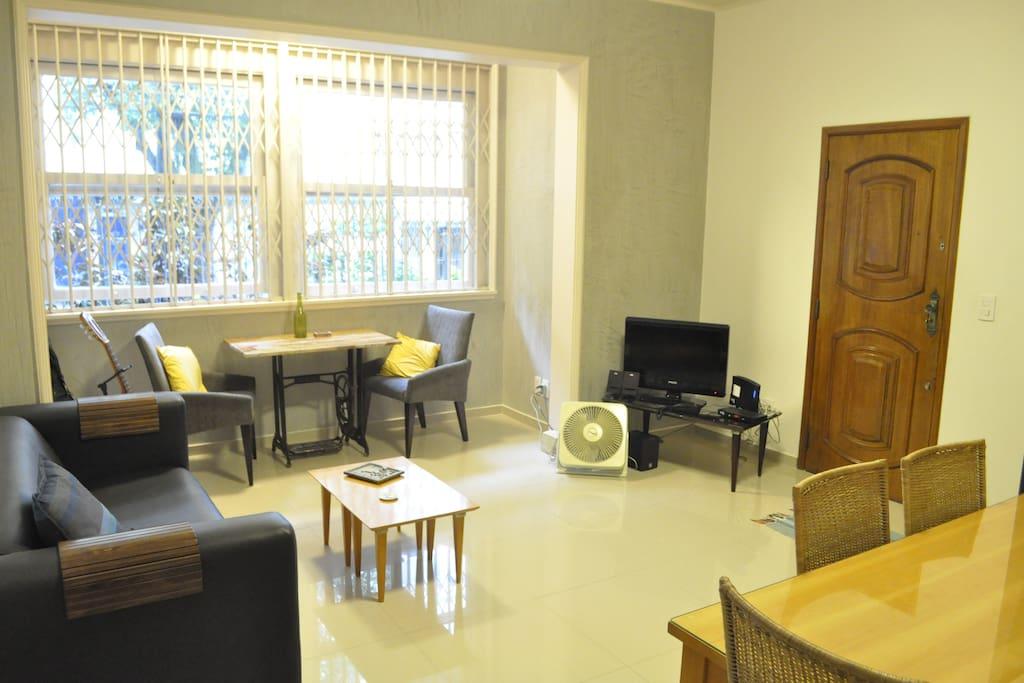 Sala de estar com televisão, mesa de jantar sofá e me mesa de centro.