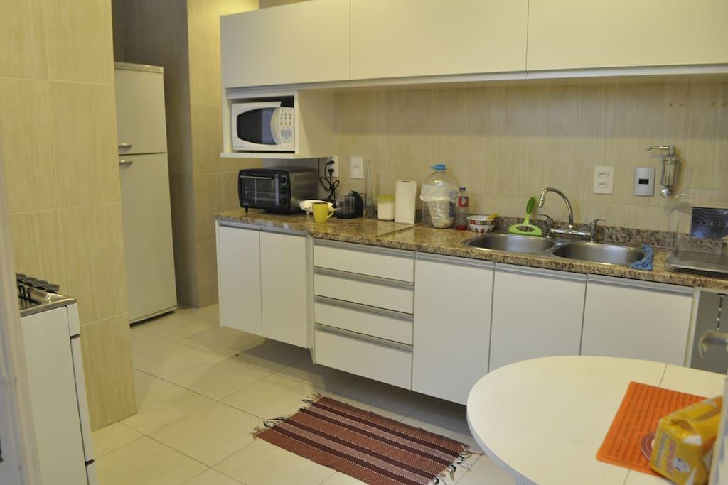 Cozinha ampla com fogão, microondas, forno elétrico, mesa, além de diversos utensílios para cozinhar.