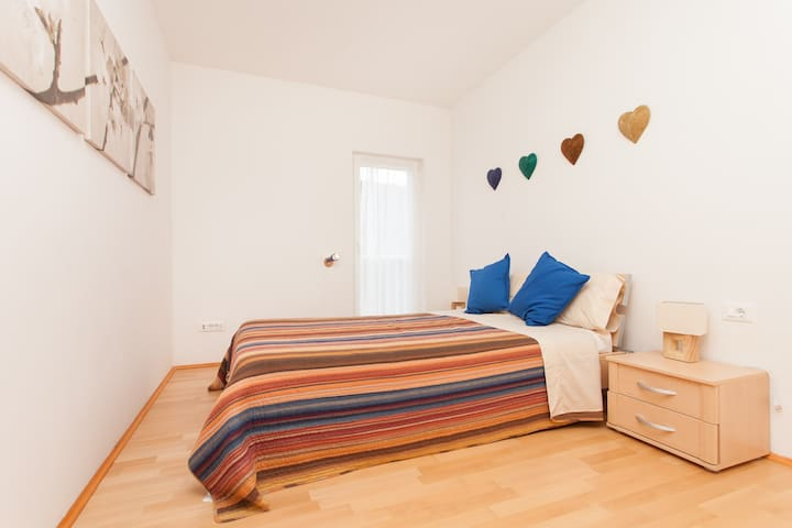 Large double bedroom with view of pool and tree covered mountain, extra pull out child's bed or cot available to fit here