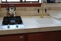Kitchen has a mini-fridge, microwave, counter-top oven/broiler, & two-burner gas stove.