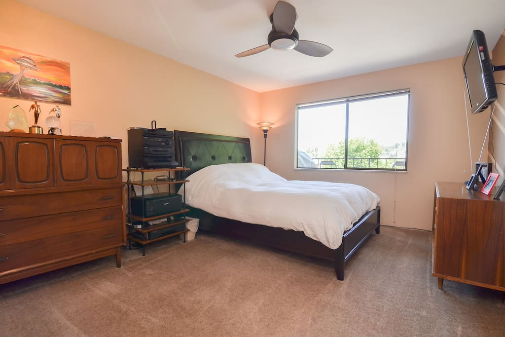 Spacious bedroom with queen sized pillow-top bed, remote control fan/light and TV for your comfort.