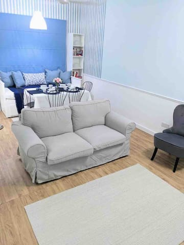 The living area includes a two-seater comfy sofa and an armchair