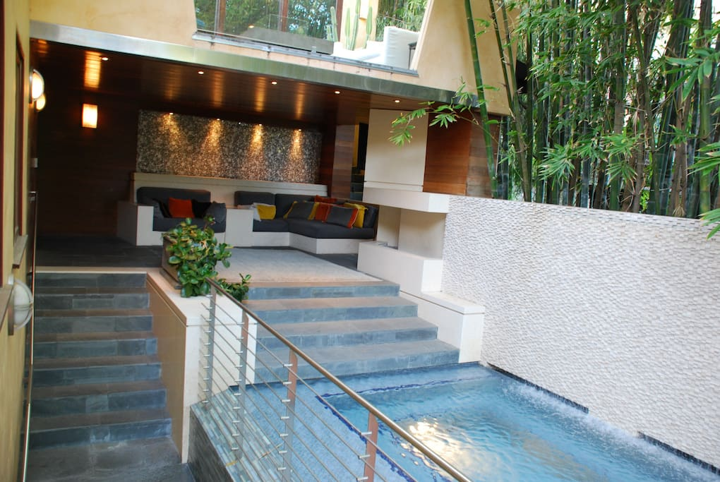 Entry steps lead to covered Entertainment Area w/ fireplace, HD TV, Wet Bar, Heated glass tiled spa (for 10), and cool breezes.