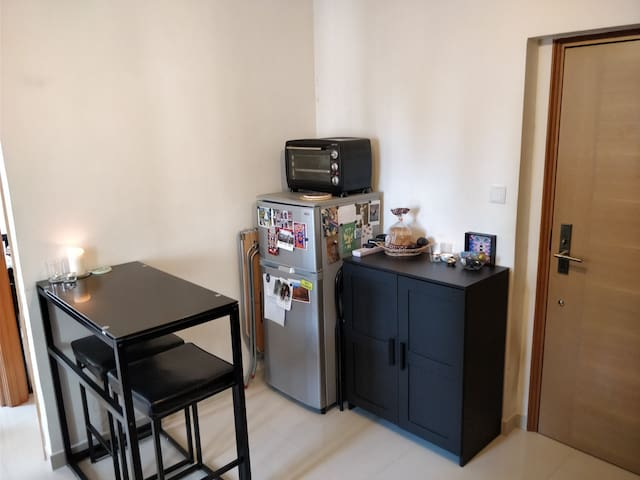 Bar table, refrigerator, and small oven.